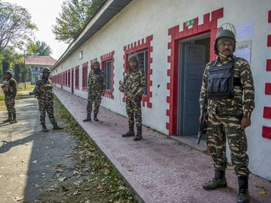 Srinagar: Security personnel stand guard at a deserted polling station during third phase of elections for urban local bodies, in Srinagar, Saturday. PTI