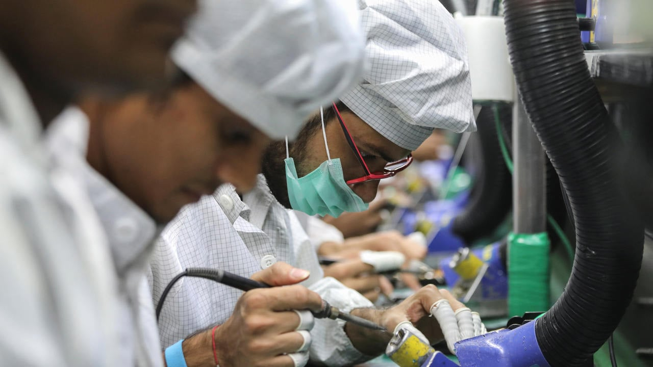 Workers solder wires on printed circuit boards of a mobile handset at Lava International Limited's manufacturing plant in Noida, India. Image: Reuters