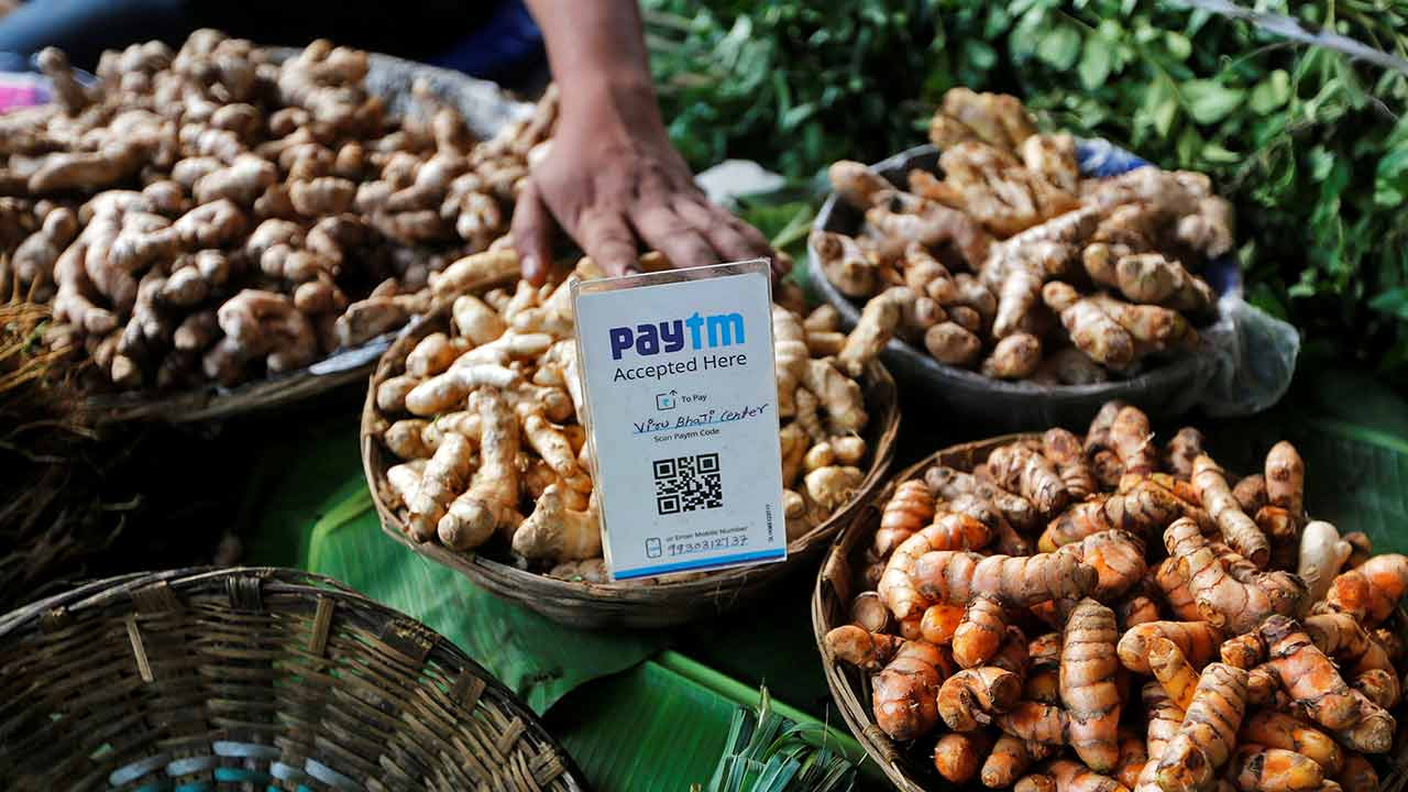 An advertisement board displaying a QR code for Paytm, a digital wallet company, is seen placed amidst vegetables at a roadside vendor's stall in Mumbai. Reuters