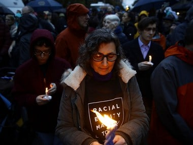 People hold candles as they gather for a vigil in the aftermath of the shooting at the Tree of Life Synagogue in Pittsburgh. AP