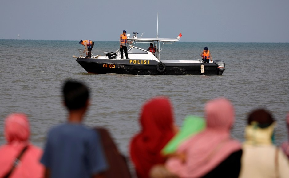 People watch rescue team members heading to the Lion Air flight JT610, sea crash location in the north coast of Karawang regency, West Java province. Reuters