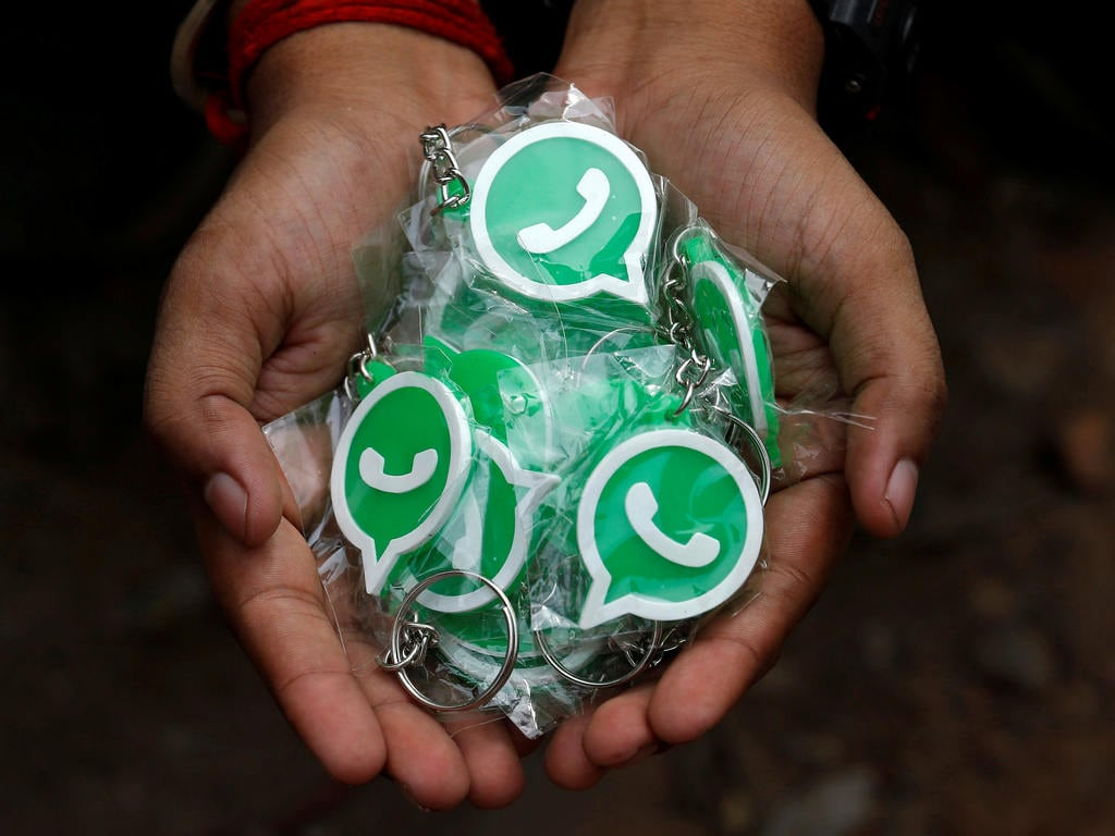A representative of WhatsApp-Reliance Jio displays key rings bearing the WhatsApp logo. Image: Reuters
