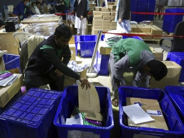 Afghan election workers secure ballots in boxes before distribution, ahead of parliamentary elections. AP