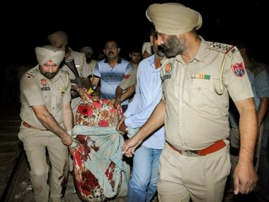 Police and volunteers in Amritsar carry a victim from the site of the train accident. PTI
