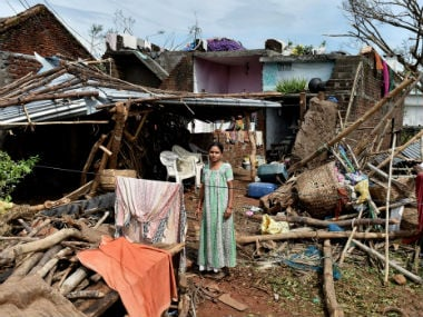 A woman stands near her damaged house hit by cyclone 'Titli', in Srikakulam. PTI