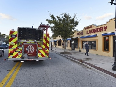 Jacksonville Fire and Rescue personnel use chemicals and hoses to clean the blood outside the Maytag Coin Laundry after a street shooting earlier in the day. AP