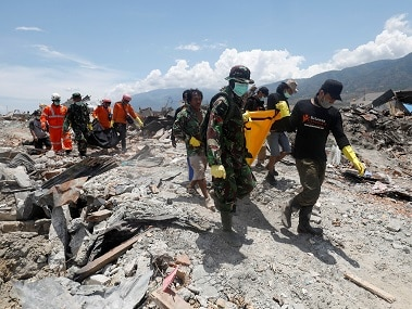 Rescuers recover bodies after Indonesia's earthquake and tsunami. Reuters