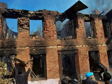 People in Kulgam clearing debris from the  damaged house where militants were hiding during an encounter. PTI