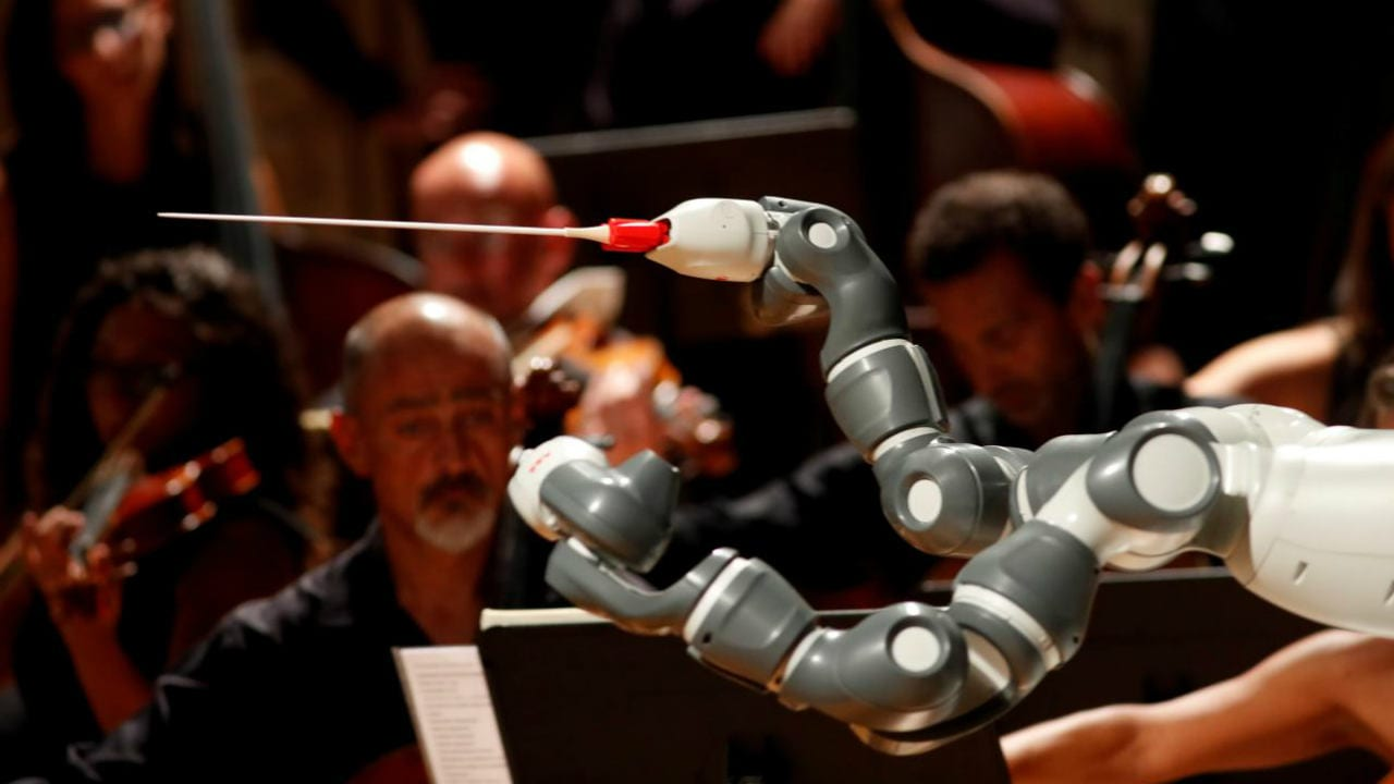 Humanoid robot YuMi conducts the Lucca Philharmonic Orchestra performing a concert alongside Italian tenor Andrea Bocelli (unseen) at the Verdi Theatre in Pisa, Italy September 12, 2017. REUTERS/Remo Casilli/File Photo