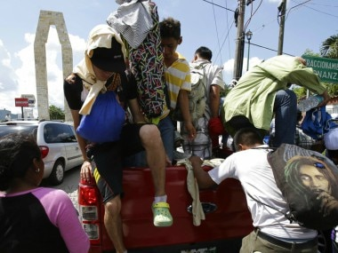 Central American migrants making their way to the US in a large caravan exit the truck of a driver who gave them a free ride to Mexico. AP