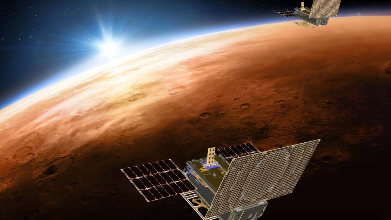 An artistic rendition of the twin Mars Cube One (MarCO) satellites flying over Mars. The MarCOs will be the first CubeSats, a kind of modular, mini-satellite, flown into deep space. They're designed to fly along behind NASA's InSight lander on its cruise to Mars.
