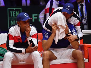 France's Jo-Wilfried Tsonga (right) is comforted by team captain Yannick Noah (left) and a teammate after his defeat to Marin Cilic. AFP