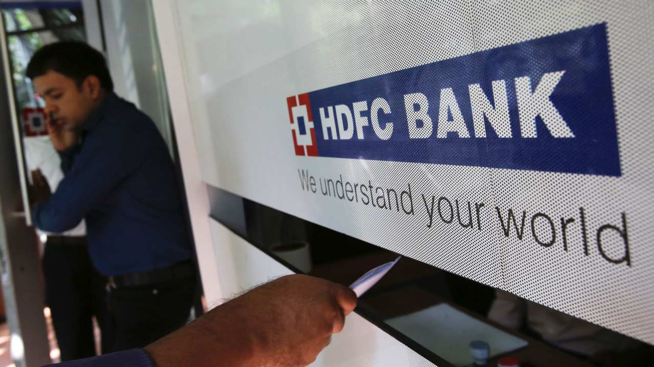 A customer walks out of a HDFC Bank branch as another deposits a cheque at a counter in Mumbai. Image: Reuters
