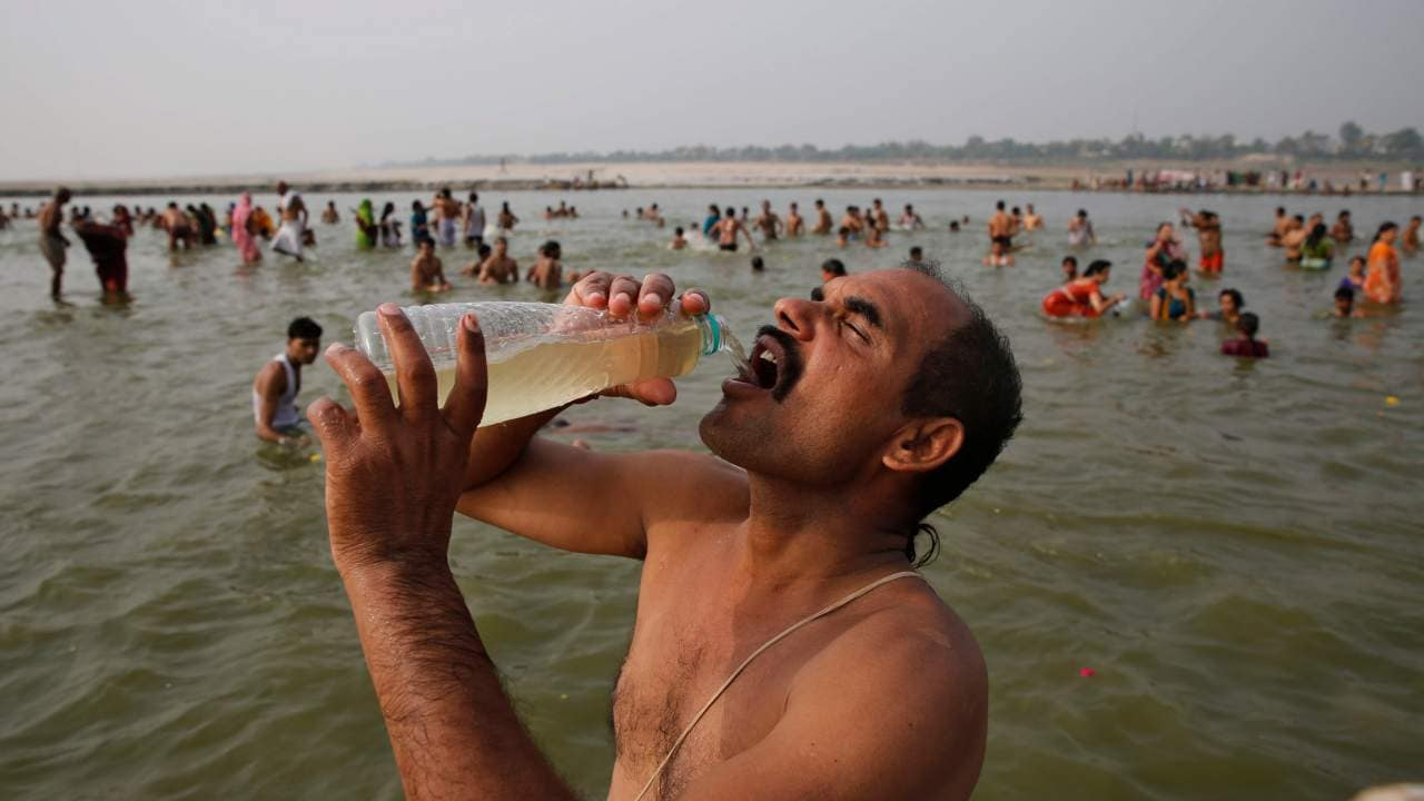 A man drinks water as others take a dip in the river Ganga, during Dussehra in Allahabad, India, June 2014. Allahabad in where the Ganga and Yamuna meet. AP