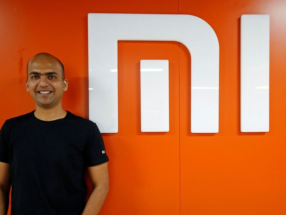 Manu Kumar Jain, Managing Director of Xiaomi India, poses next to the logo of Xiaomi in his office in Bengaluru. Image: Reuters