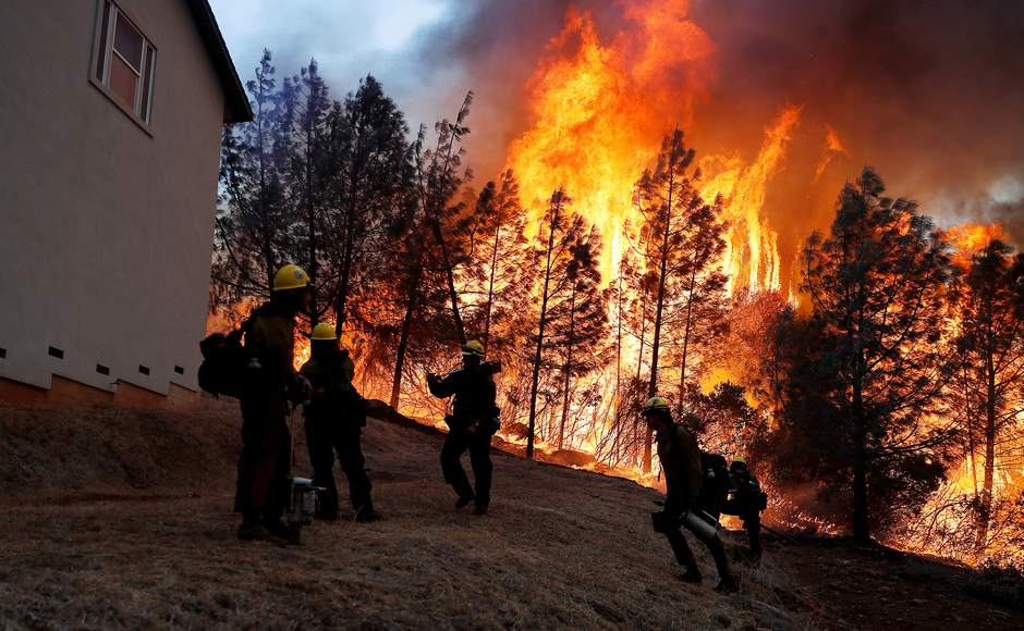 Wildfires raged in parts of California. A group of US Forest Service firefighters monitor a back fire while battling to save homes at Paradise, California. Reurters