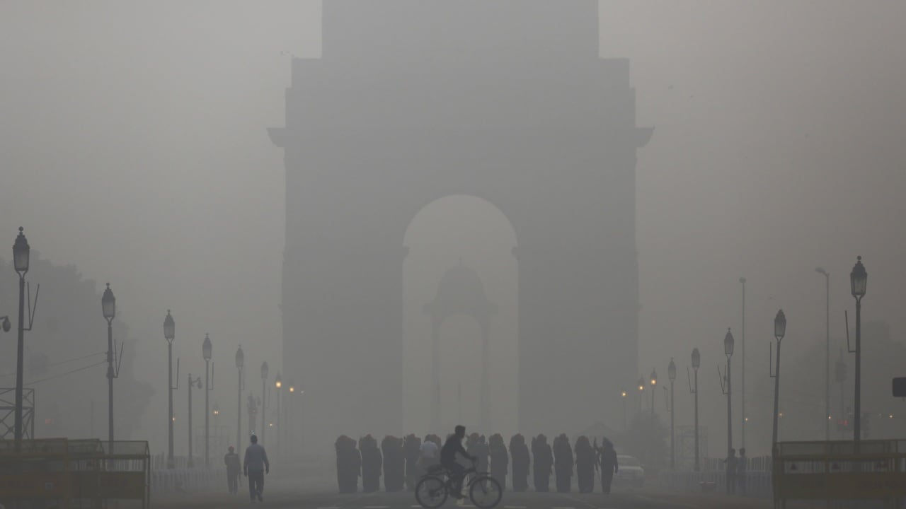 A man rides his bicycle next to Indian soldiers marching in front of India Gate on a smoggy morning in New Delhi. Reuters