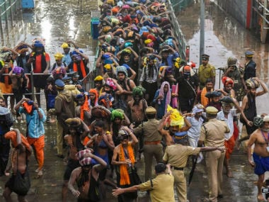 Devotees enter the Sabarimala temple as it opens amid tight security. PTI