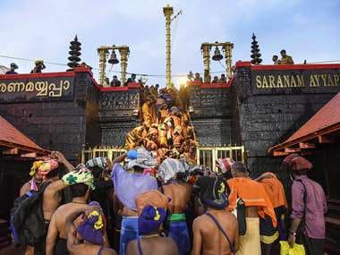 Devotees enter the Sabarimala temple as it opens amid tight security on Friday. PTI