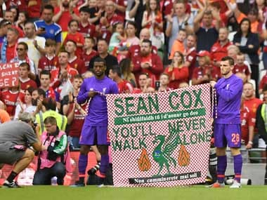 Liverpool players hold aloft a banner for Sean Cox at a pre-season friendly. Reuters