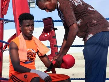 Somali boxer Abdi-aziz Ali Shirar, 21-years-old, is helped with his glove by his coach during a boxing match. AFP
