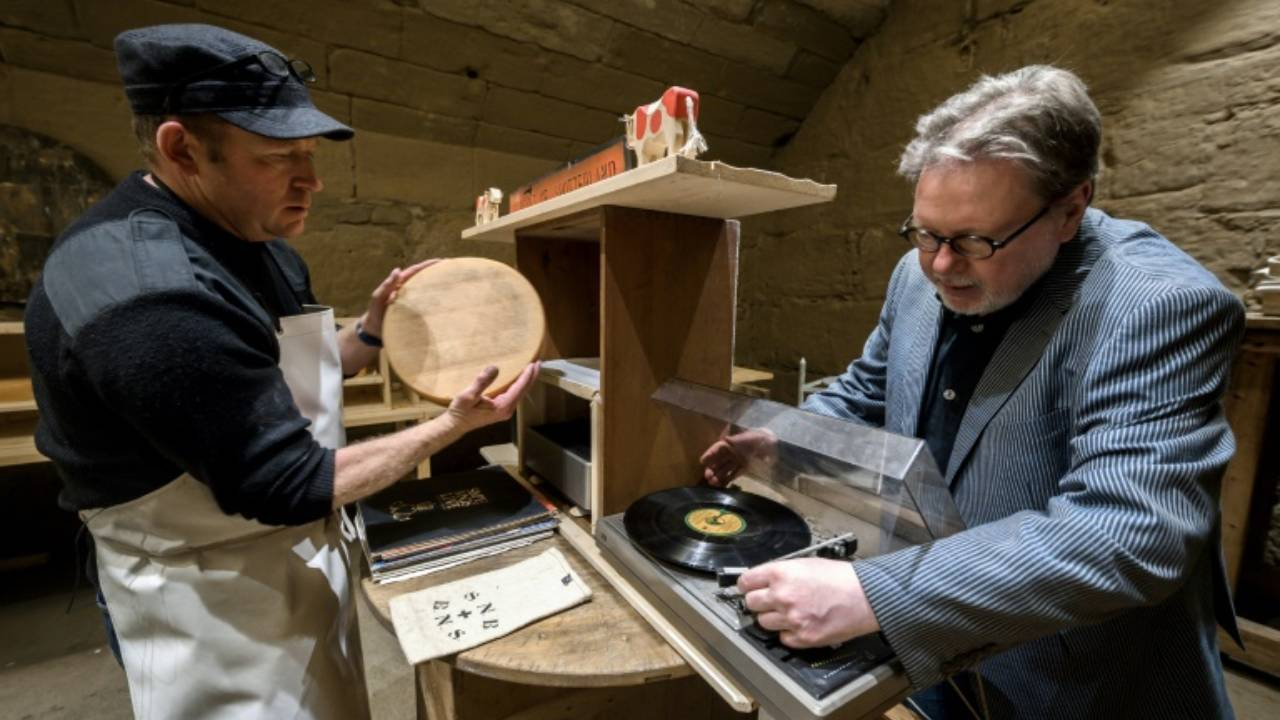 Swiss cheesemaker Wampfler (left) and director of the Music Department at University of the Arts in Bern, Michael Harenberg pose with a vynil record and wheel of Emmental. AFP