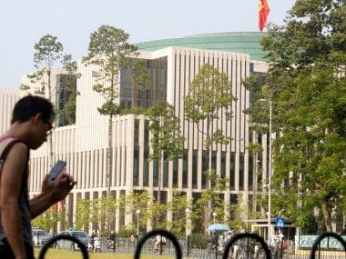 Tourists walk past Vietnam's National Assembly (Parliament) building in Hanoi. Reuters