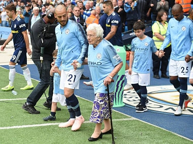 Manchester City's David Silva (L) holds the hand of 102-year-old mascot Vera Cohen. AFP