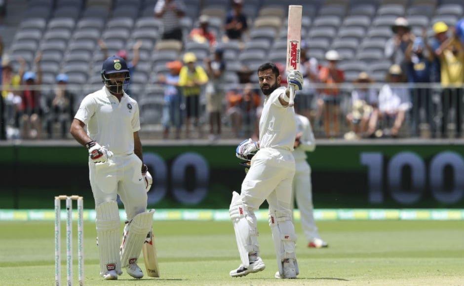 Virat Kohli raises his bat after slamming his 25th Test century. AP