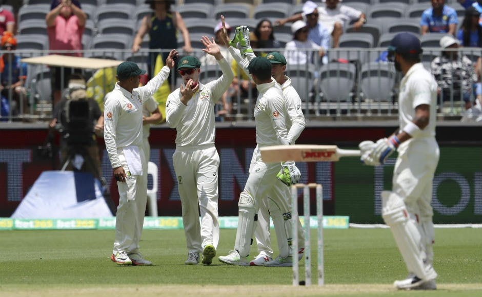 Peter Handscomb celebrates with teammates after collecting a low catch to dismiss Virat Kohli. AP