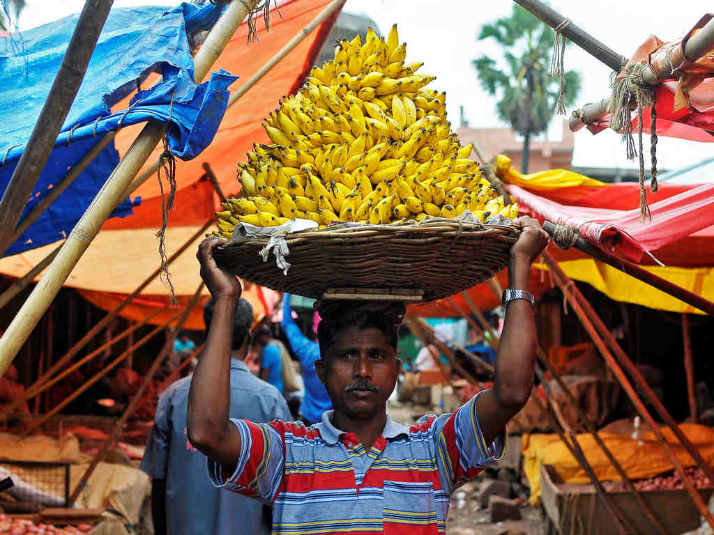 A labourer carries a basket of bananas inside a wholesale fruit and vegetable market in Bengaluru, India, August 22, 2016. REUTERS/ Abhishek N. Chinnappa - S1BETWWQYUAA
