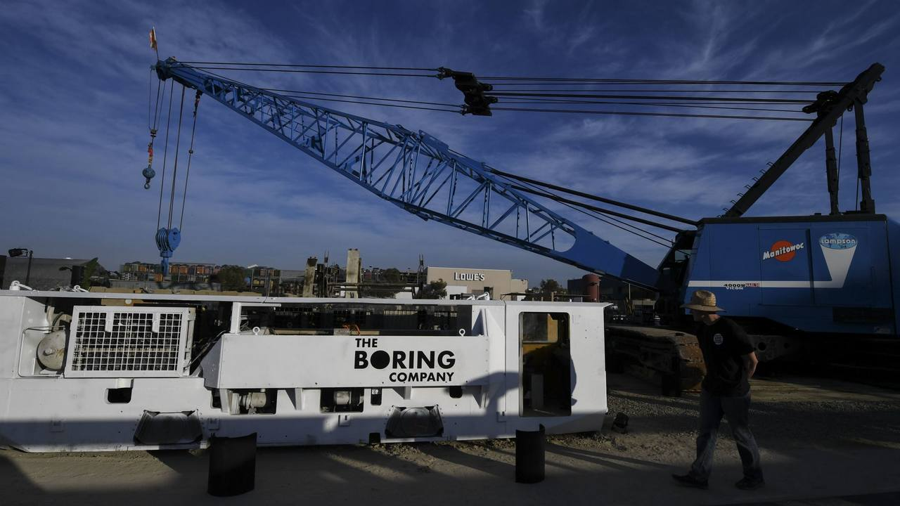 Electric locomotives and tunnel boring equipment are displayed before an unveiling event. Image: AP