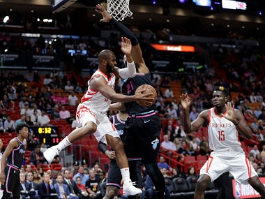 Houston Rockets guard Chris Paul, left, passes to center Clint Capela (15) as Miami Heat center Hassan Whiteside defends during the first half of an NBA basketball game, Thursday, Dec. 20, 2018, in Miami. (AP Photo/Lynne Sladky)