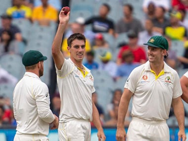 Australia's Pat Cummins, center, raises the ball after getting his 5th wicket in the 2nd innings during play on day four of the third cricket test between India and Australia in Melbourne, Australia, Saturday, Dec. 29, 2018. (AP Photo/Asanka Brendon Ratnayake)
