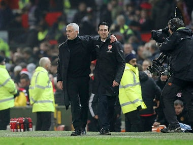 Manchester United manager Jose Mourinho, left, and Arsenal manager Unai Emery react after the final whistle during the Premier League match at Old Trafford, Manchester, Wednesday December 5, 2018. Martin Rickett/PA via AP)