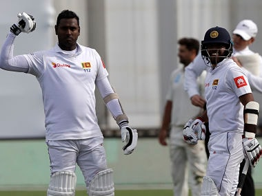 Sri Lanka's Angelo Mathews, left, celebrates after scoring a century with teammate Kusal Mendis during play on day four of the first cricket test between New Zealand and Sri Lanka in Wellington, New Zealand, Tuesday, Dec. 18, 2018. (AP Photo/Mark Baker)