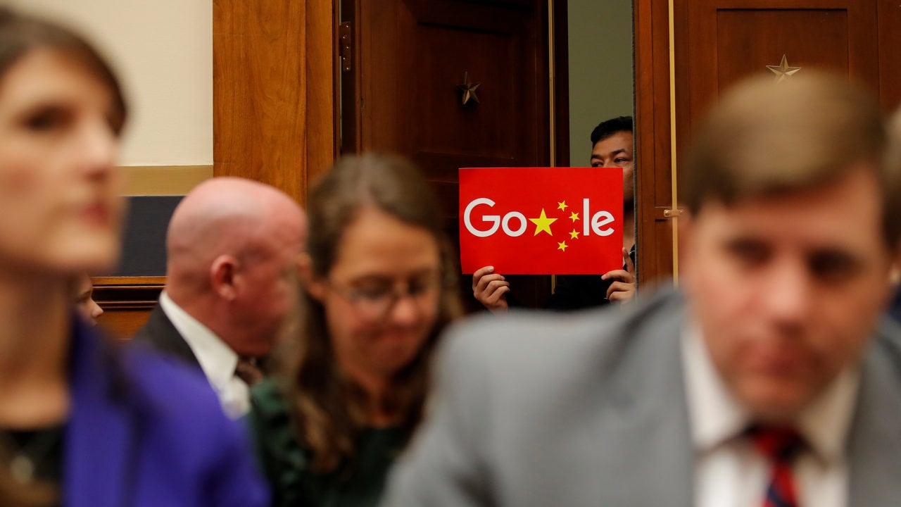 A demonstrator holds up a sign in the doorway as Google CEO Sundar Pichai testifies at a House Judiciary Committee on greater transparency. Image: Reuters