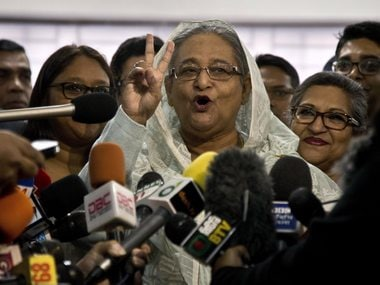 Bangladesh Prime Minister Sheikh Hasina flashes a victory sign as she speaks to the media persons after casting her vote in Dhaka. AP