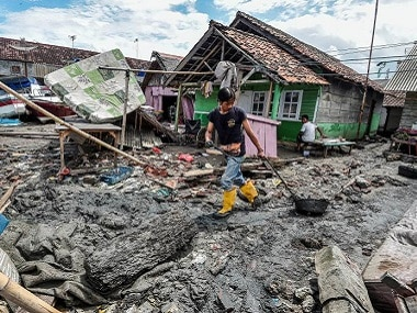 A local moves mud to clean his neighbourhood after a tsunami hit at Anyer in Banten, Indonesia. Reuters