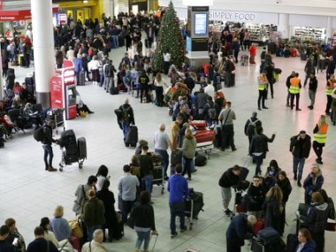 People queue at Gatwick airport, near London, as the airport remains closed with incoming flights delayed or diverted. AP
