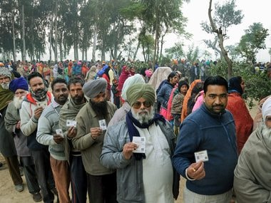 Voters standing in queues at a polling station in Punjab's Amritsar district. PTI