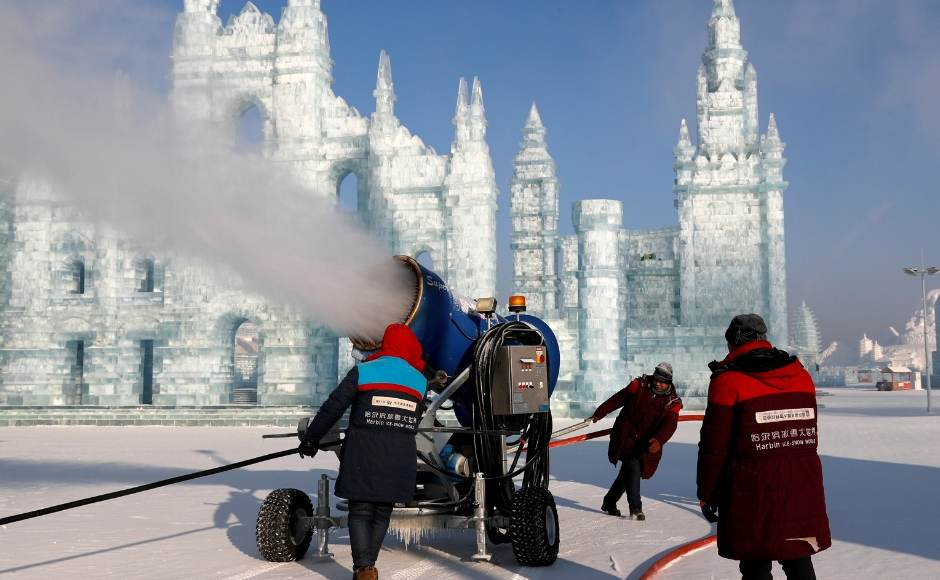 Visitors marvel at the mini ice replicas of the Colosseum and of the Milan Cathedral, particularly in the long evenings when soft, colored lights illuminate the ice sculptures. The image shows a snowmaking machine spraying artificial snow in front of the sculptures. Reuters