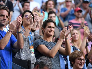 Amelie Mauresmo (C) coach of France's Lucas Pouille celebrates with others after he beat Canada's Milos Raonic in their men's singles quarter-final match on day ten of the Australian Open tennis tournament in Melbourne on January 23, 2019. (Photo by William WEST / AFP) / -- IMAGE RESTRICTED TO EDITORIAL USE - STRICTLY NO COMMERCIAL USE --