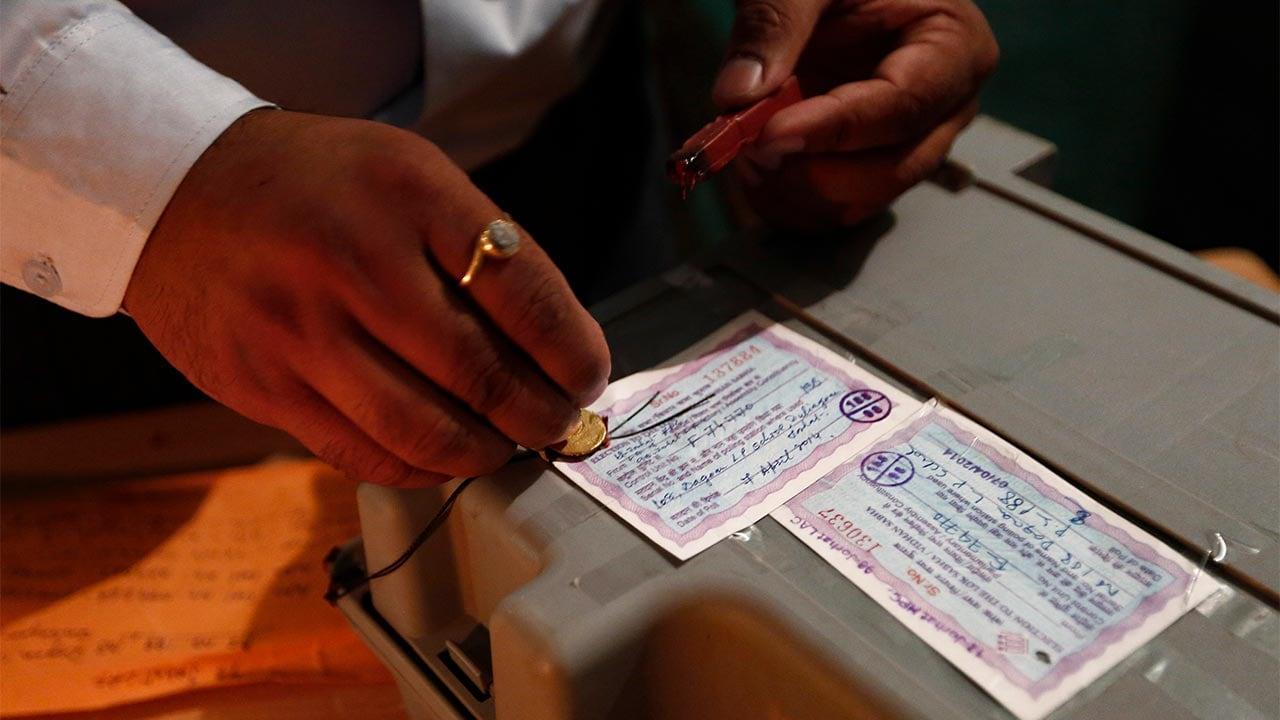 A polling official seals an EVM. Image: Reuters
