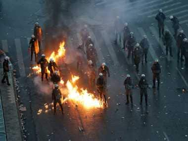 A molotov cocktail explodes next to Greek riot police during clashes after a rally in Athens, Sunday. AP