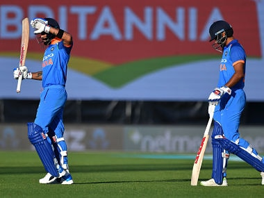 India's captain Virat Kohli (L) walks from the field with teammate Shikhar Dhawan after the fierce setting sun halted play during the first ODI. AFP