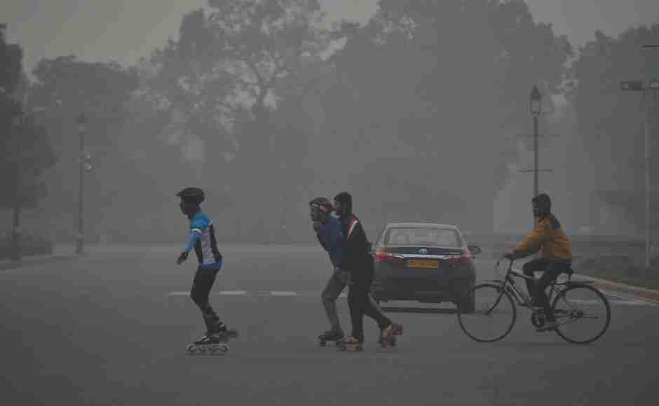 Skaters cross a road near Raisina Hills in New Delhi on a cold, foggy morning. PTI