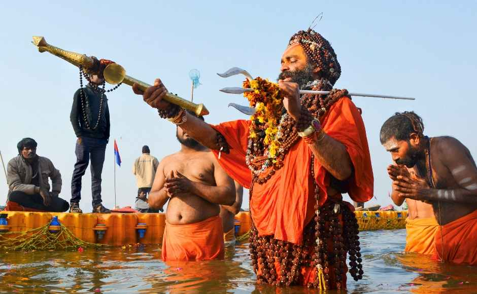 A sadhu holds a trident as he takes a holy dip at Sangam on the occasion of 'Paush Purnima'. PTI