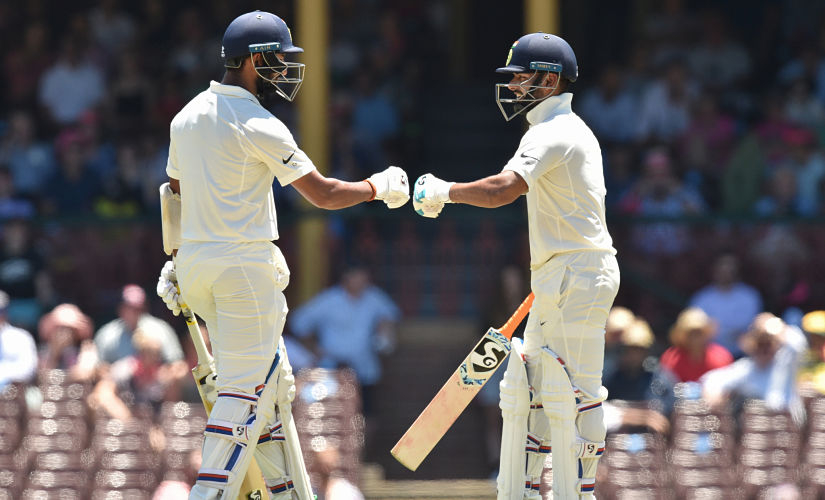 India batsman Cheteshwar Pujara (L) and Rishabh Pant (R) touch gloves between overs on the second day of the fourth and final cricket Test against Australia at the Sydney Cricket Ground on January 4, 2019. (Photo by PETER PARKS / AFP) / -- IMAGE RESTRICTED TO EDITORIAL USE - STRICTLY NO COMMERCIAL USE --