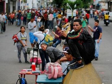 Venezuelans line up outside of the migration office in San Antonio. AP